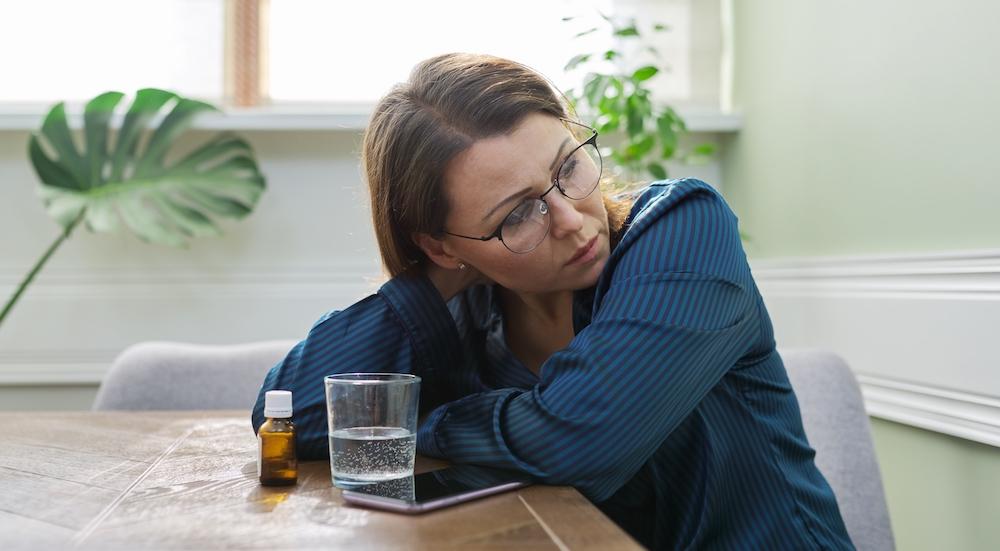 Frau in Wechseljahren sitzt am Tisch mit Medikamenten und wasserglas leidet an Schlafstörungen