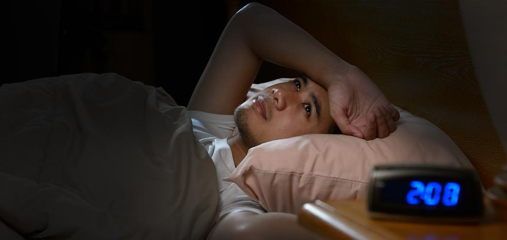 mann liegt wach im bett leidet an schlaflosikeit