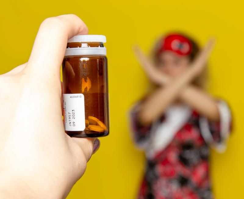 junge frau mit Schlafmaske unschaft im Hintergrund mit weiblicherhand im Vordergrund hält eine Dose mit Schlafmitteln