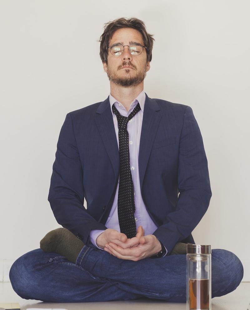 junger Geschäftsmann beim Stress abbauen durch Meditation um seine Schlafstörungen zu behanden