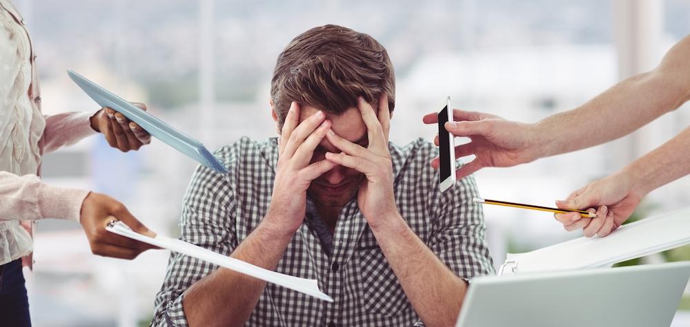 junger mann am Arbeitsplatz kann seinen Stress nicht abbauen leidet dadurch an Schlafproblemen