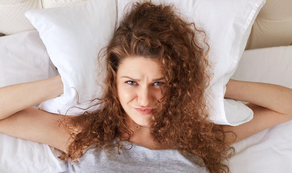 draufsicht frau liegt wach im Bett kann nicht einschlafen