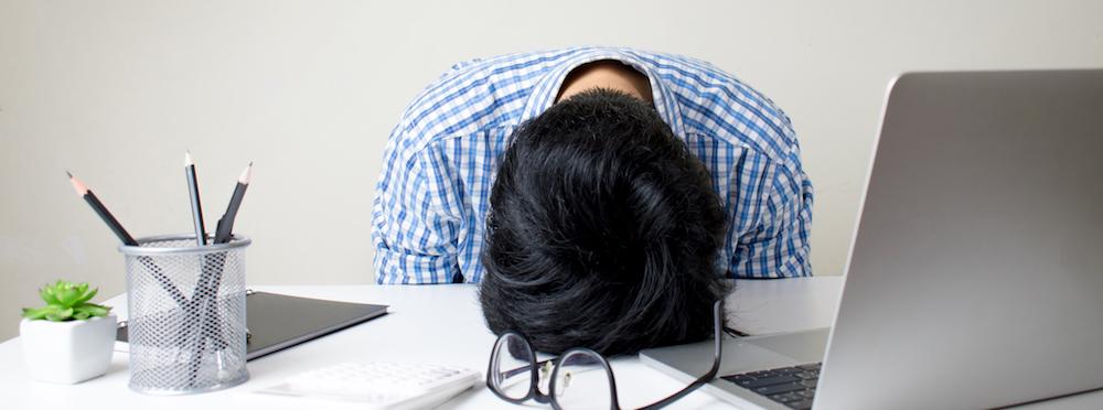 gestresster junger geschäftsmann am arbeitsplatz hat Schlafprobleme
