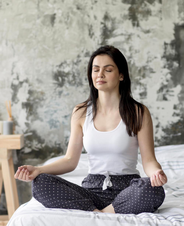 frau macht yoga übeungen auf dem Bett als hausmittel gegen schlafprobleme