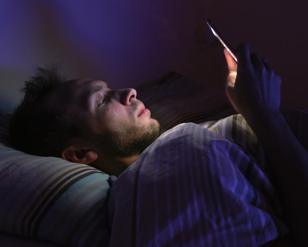 junger mann liegt im bett und spielt mit smartphone leidet an Einschlafstörungen