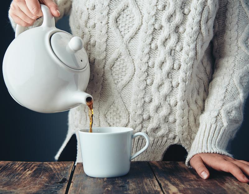 frau im strickpullover gießt eine kanne Tee zum einschlafen