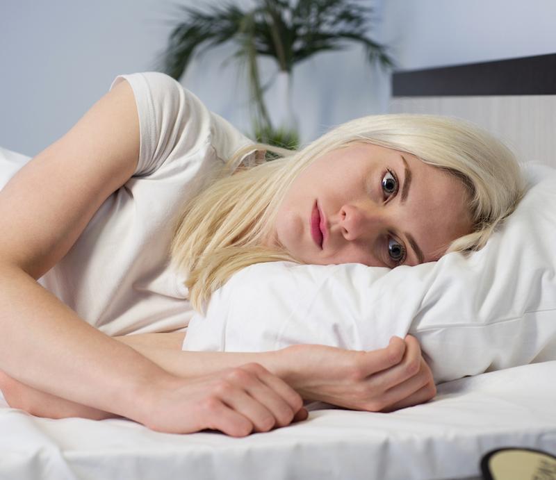 Frau liegt im Bett wach Augen geöffnet hat Einschlafstörungen