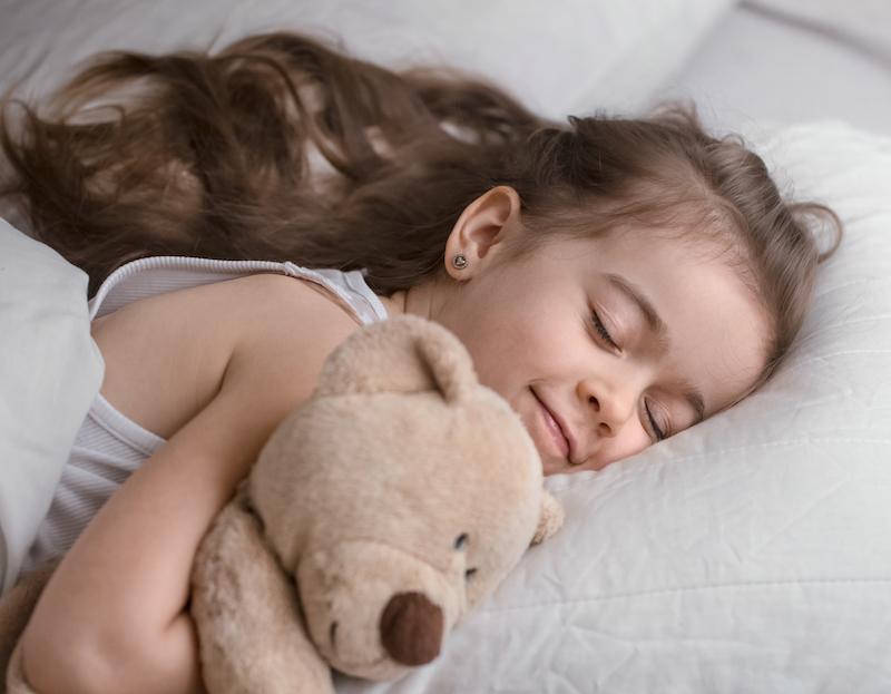 kleines Mädchen schläft mit teddy bär Schlafstörungen bei Kindern