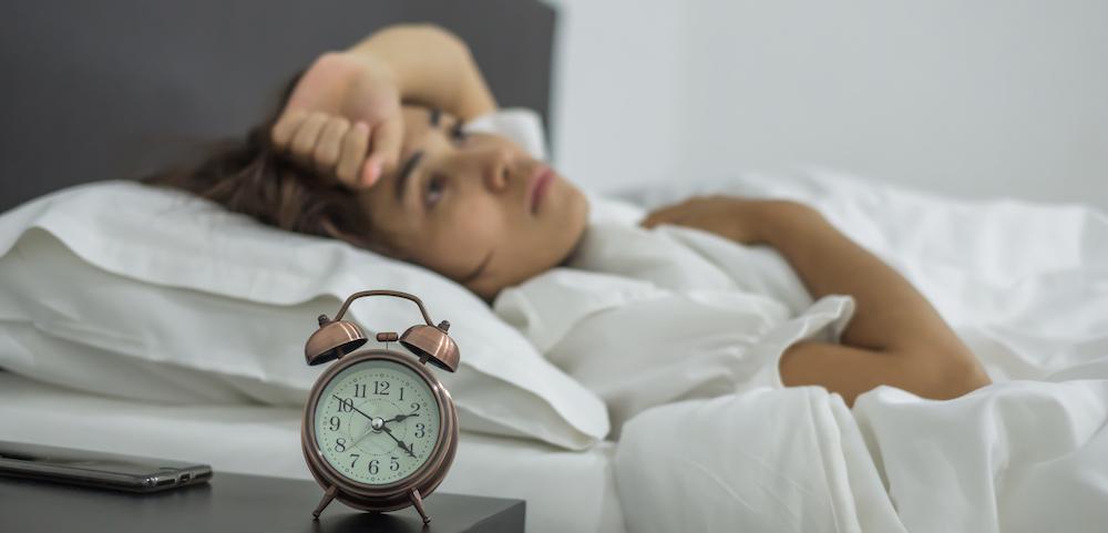junge Frau im Bett leidet an Schlafstörungen und Insomnie kann nicht einschlafen