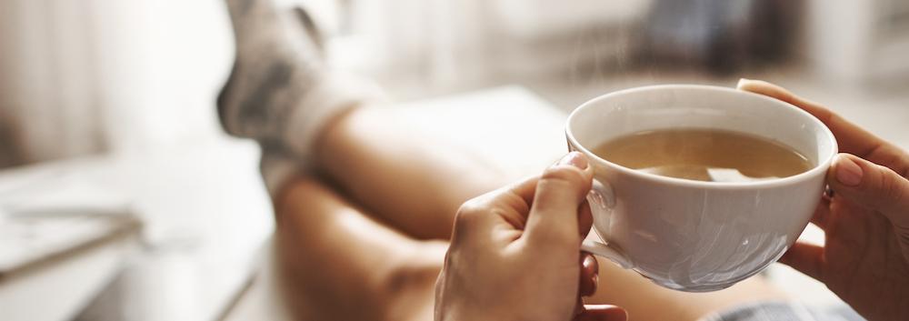 frau entspannt sich mit Tee als hausmittel gegen schlafprobleme