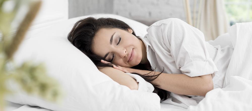 frau schläft im bett gesund schlafen