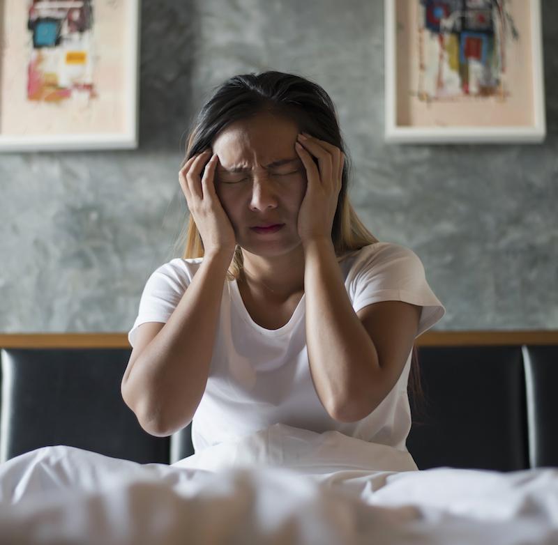frau sitzt im Bett und leidet an Ursachen von Schlafstörungen hat Kopfschmerzen und hält sich den Kopf