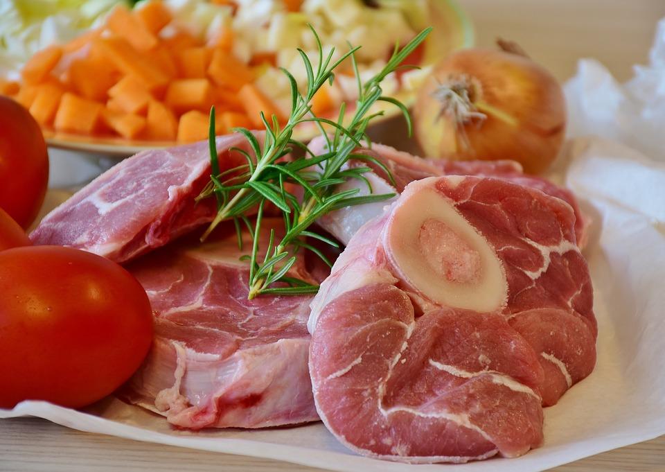 Eiweiße - Rohes Fleisch mit Knochen und Esstisch