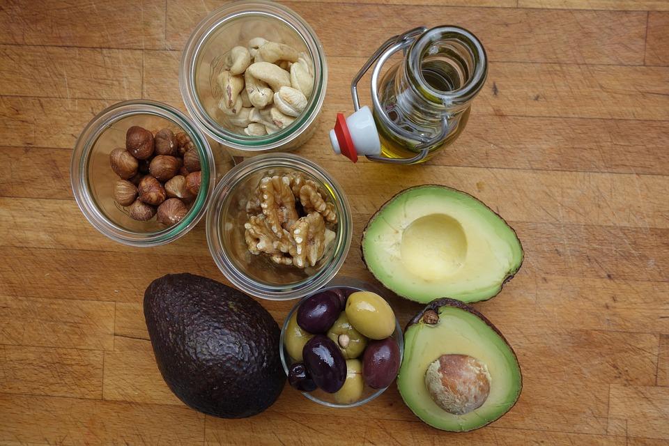 Gesunde Fette in Form von Öl und Nüssen auf einem Holztisch