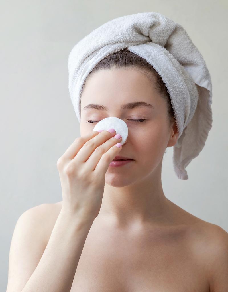 Beauty Portrait Frau mit Handtuch und gesunder Haut benutzt Wattepad gegen Eiterpickel