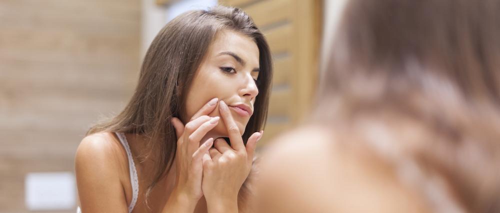 Junge Frau steht vor Spiegel drückt Eiterpickel aus