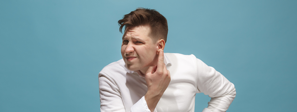 Mann im weißem Hemd hat Schmerzen durch Pickel im Ohr