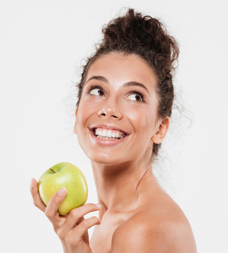 lächelnde frau mit gesunder haut hält Apfel ernährung