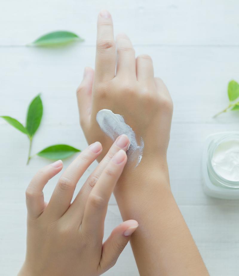 Zinksalbe gegen Pickel sorgt für gesunde Haut auf Hand über weißem Tsch