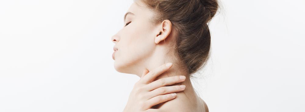 Schöne Frau vor einem weißem Hintergrund verdeckt Pickel am Hals mit rechter Hand