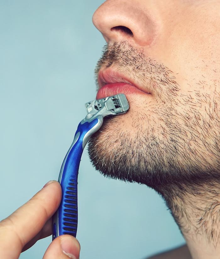 Mann rasiert Bart trocken als Ursache von Pickel am Hals