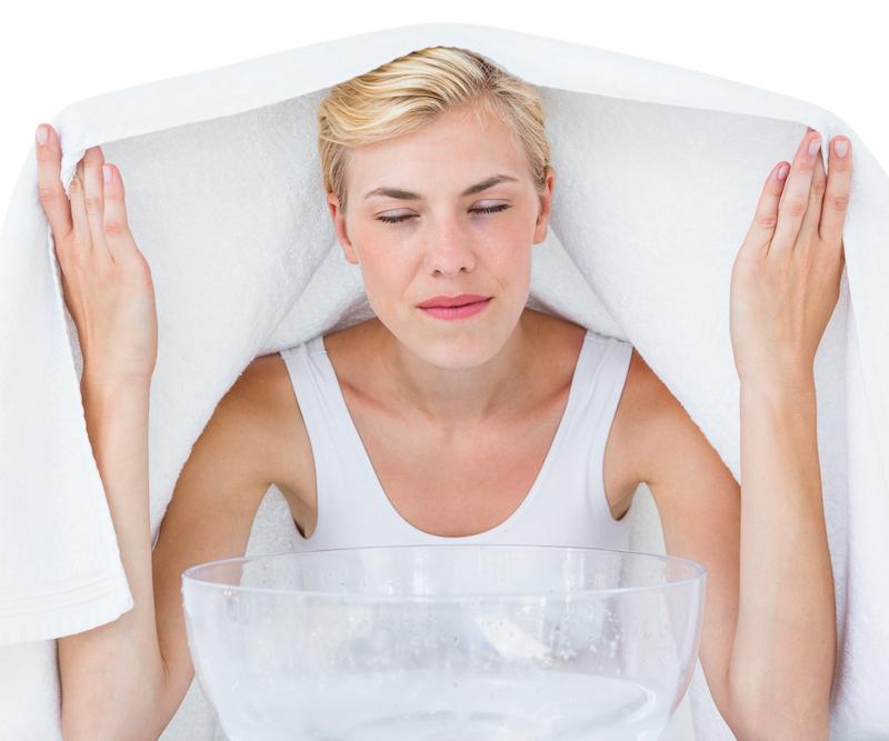 Blonde Frau mit kurzen Haaren inhaliert Dampfbad mit Teebaumöl zur Behandlung gegen Pickel