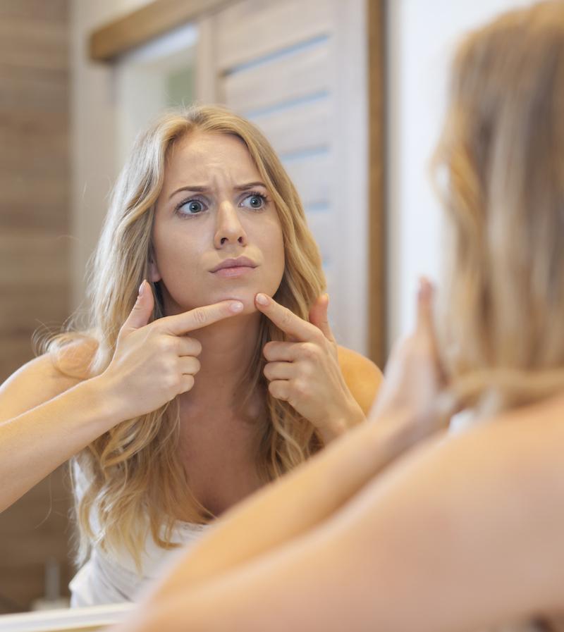 Junge Frau drückt unterirdischen Pickel am Kinn aus vor Spiegel