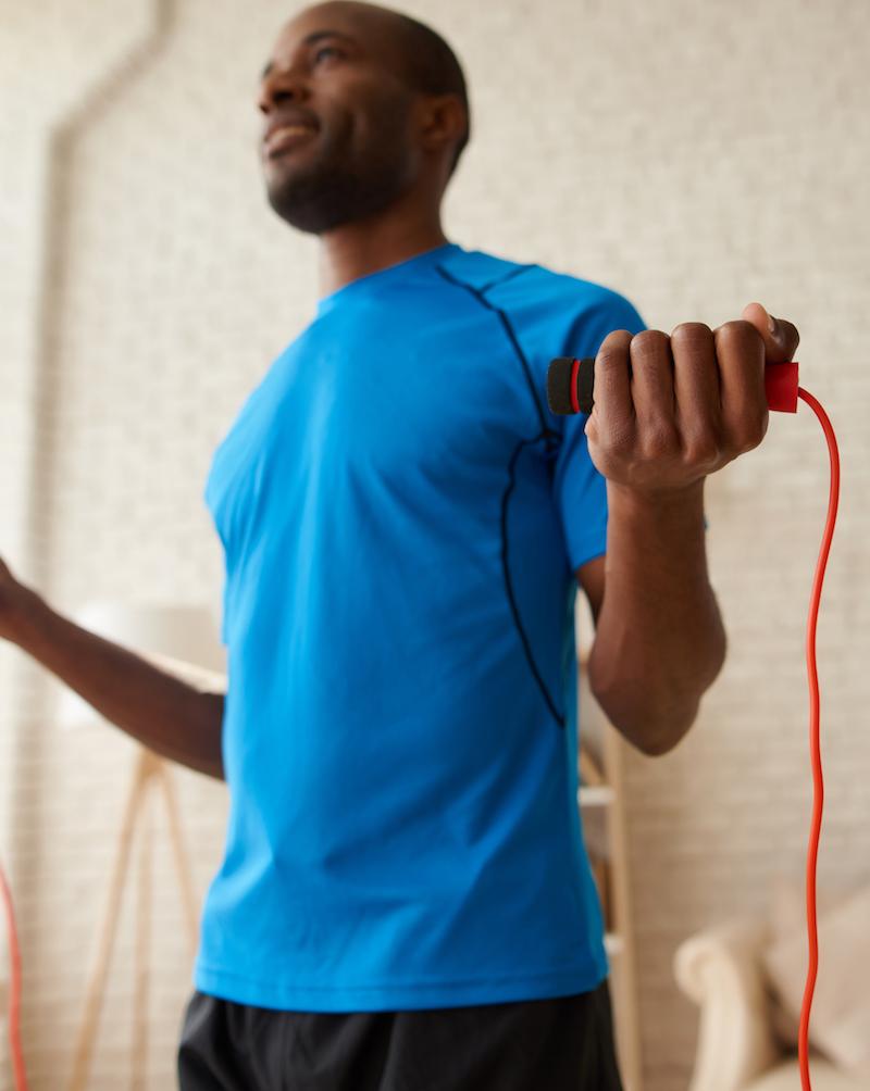 sportlicher mann der zuhause Fitness mit einem Springseil macht