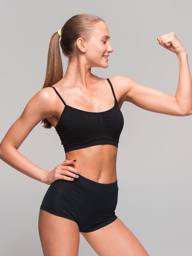 sportliche junge Frau erfolgreich muskelaufbau steht seitlich und spannt ihren bizeps an