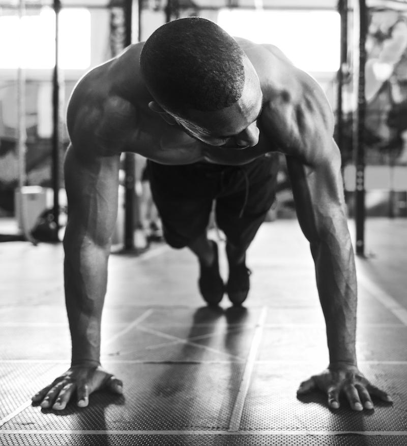 athletischer mann macht Liegestütze im fitness studio schwarz weiß bild