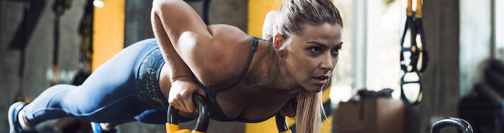 junge frau training ihre muskeln mit kettelbell liegestütze