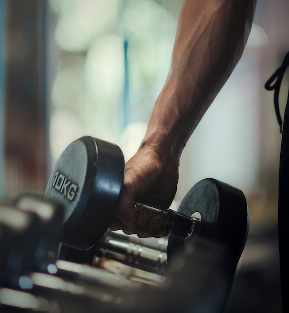 Mann hebt eine zehn Kilogrammm Hantel im Fitness studio