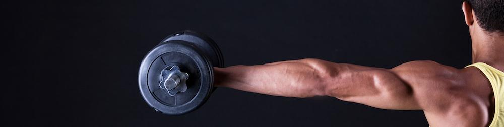 starker muskulöser Mann mit ausgestrecktem Arm und Kurzhantel in der Hand