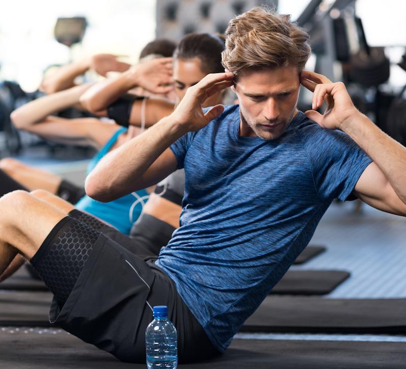 junger mann macht sit up als bauchmuskeltraining im fitness studio