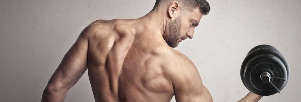 gut aussehender Mann zeigt seine rücken Muskeln und hebt eine Kurzhantel