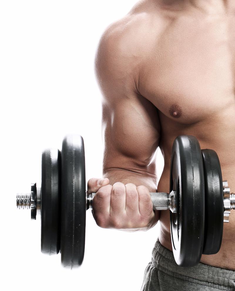 mann hält Kurzhantel in der rechten Hand und hat gut trainierte und starke arme