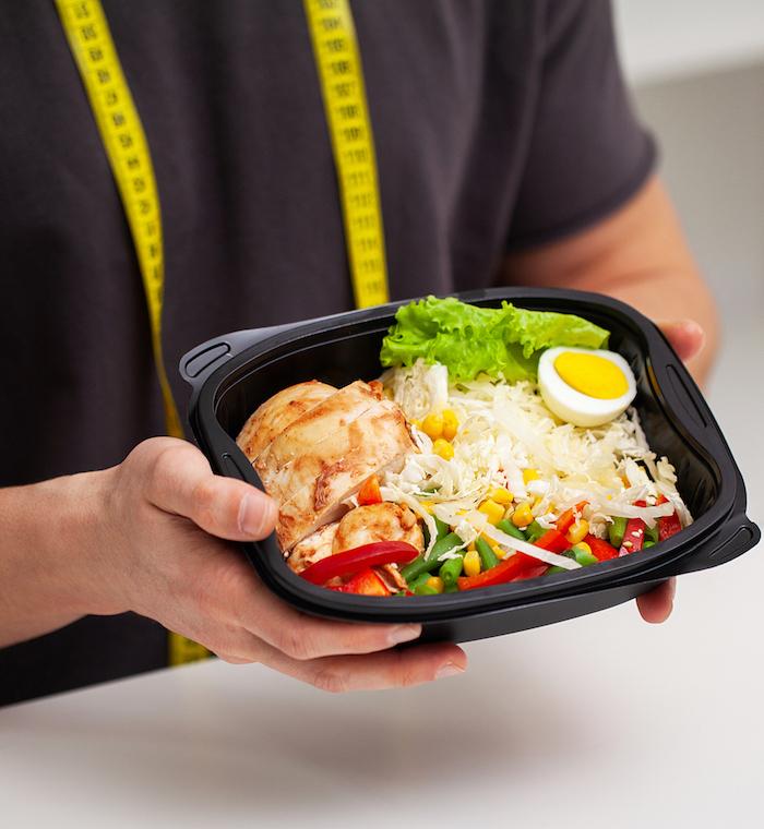 Mann hält gesundes essen zum Muskelaufbau in den Händen mit Nudeln Hähnchenfleisch Ei Salat und Gemüse