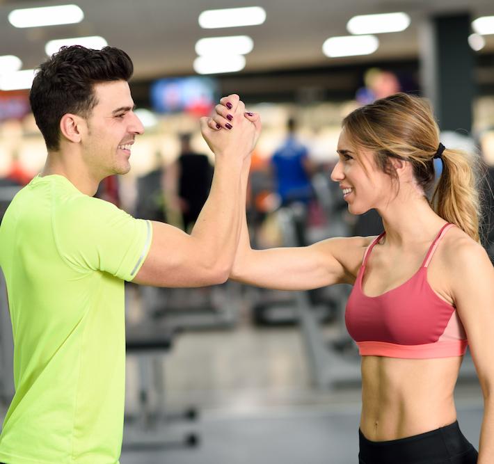 man und Frau im Fitness studio geben ein high five