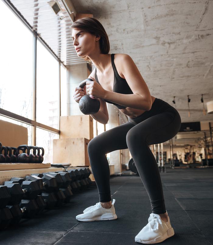 junge frau macht kniebeuge mit kettlebell trainiert muskeln im Oberschenkel im fitness studio