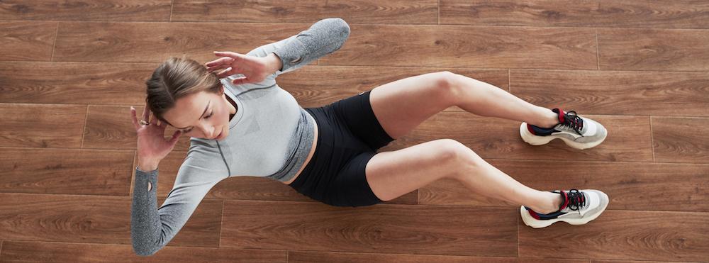 junge sportliche frau macht bauchmuskeltraining auf holzboden
