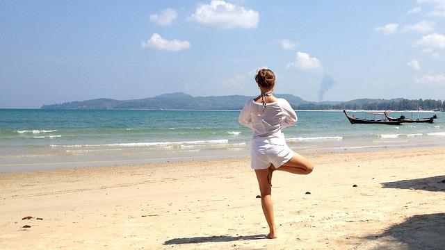 Frau in Yogaposistion am Strand