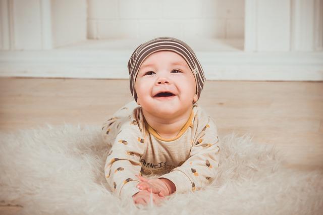 Baby liegt auf dem Boden und lacht.